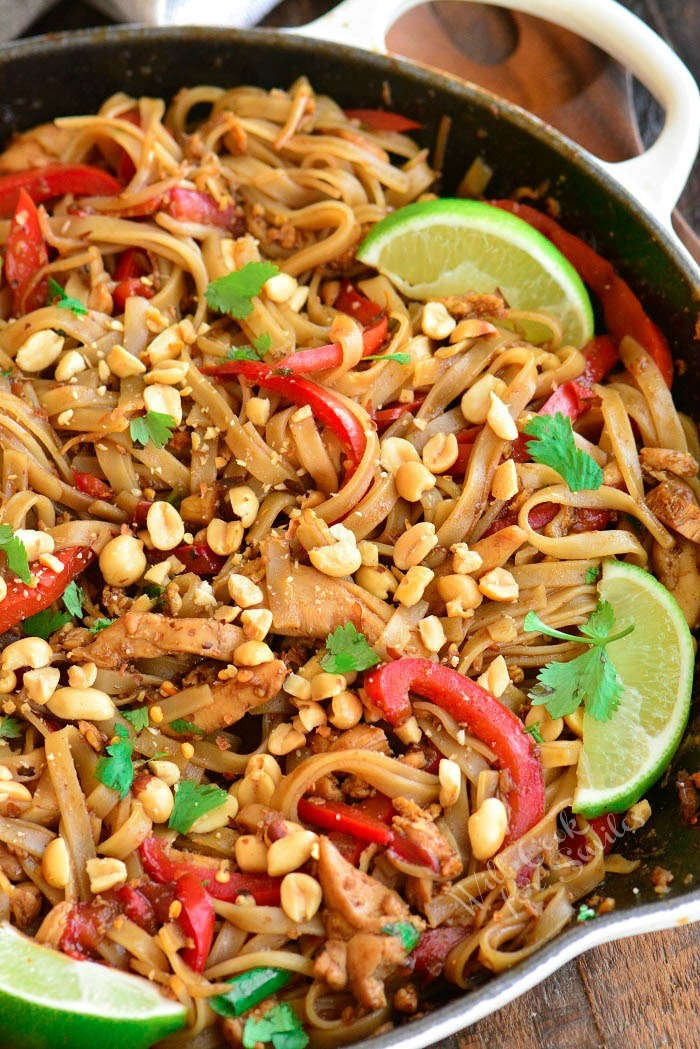 close up of cooked pad thai in a pan topped with peanuts and lime wedges
