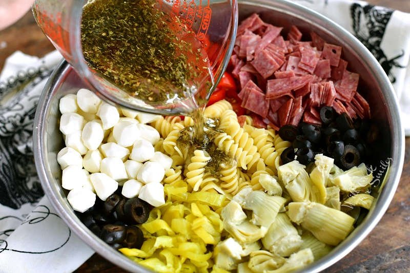 pouring dressing over Antipasto Pasta Salad in a metal bowl