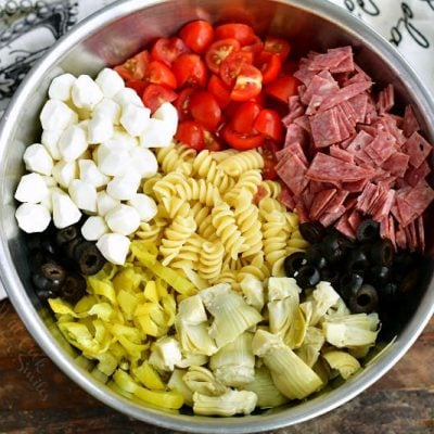 ingredients for antipasto pasta salad laid side by side in a mixing bowl