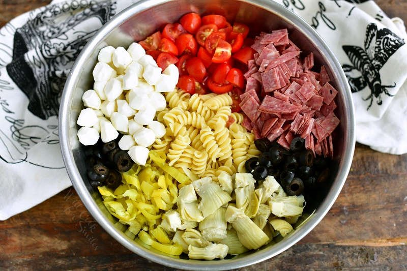 ingredients for antipasto pasta salad laid side by side in a metal mixing bowl