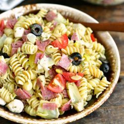 mixed pasta salad in a bowl horizontal views, wooden spoon in a bowl