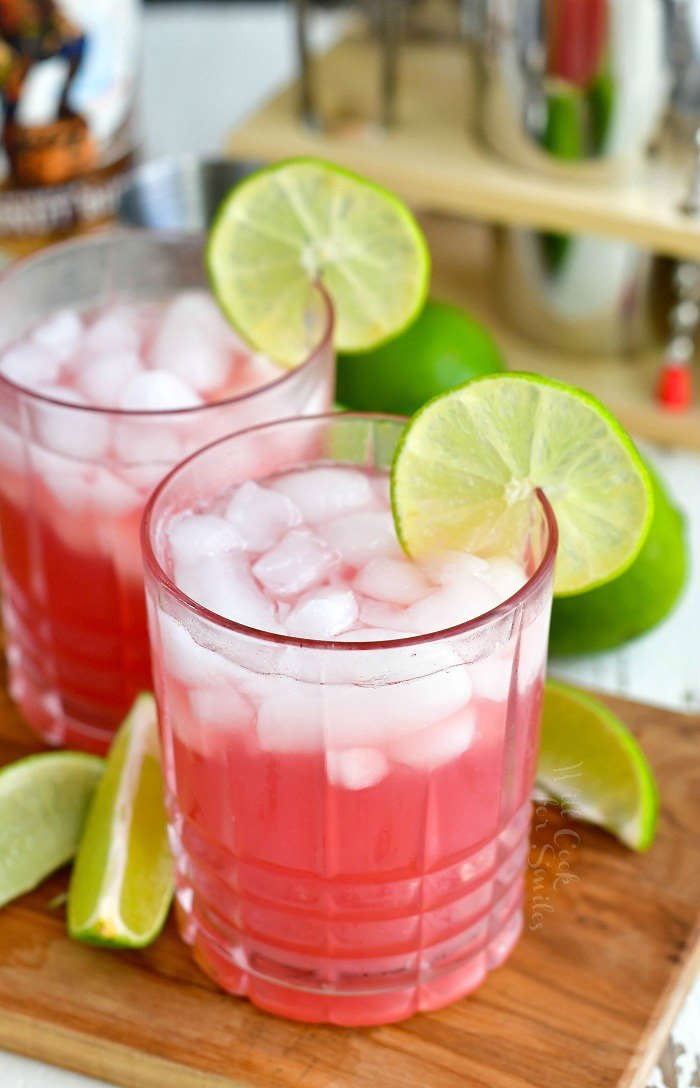 bright pink bay breeze cocktail in a glass with ice and lime slice