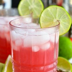 front of glass filled with bright pink cocktail and ice with lime slice on the rim