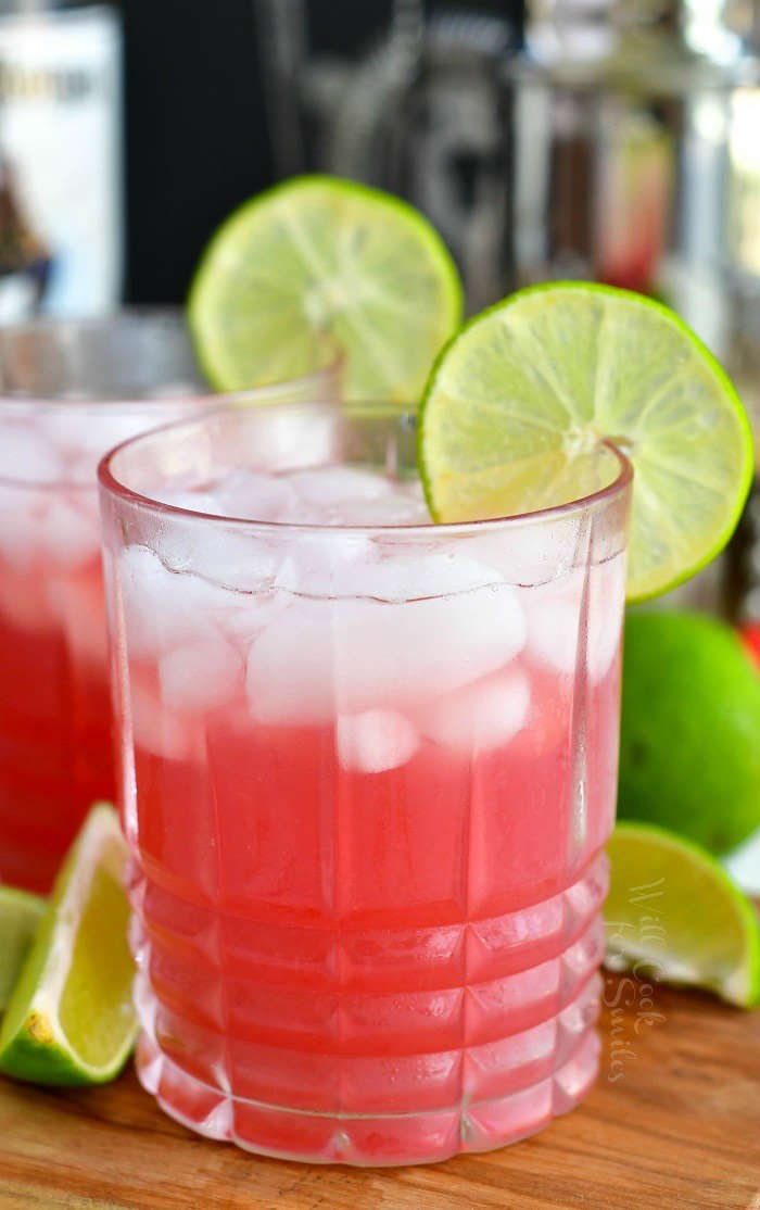 bright pink cocktail in the glass garnished with lime slice