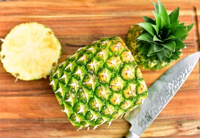 pineapple laying on the board with top and bottom cut off next to it and a knife