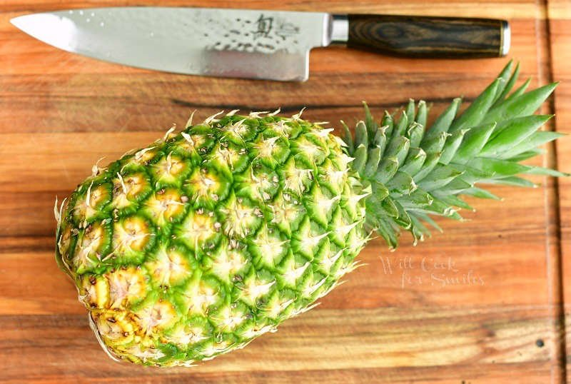 whole pineapple on a wooden cutting board with a knife next to it