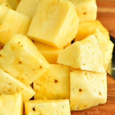 cut pineapple into chunks on a cutting board
