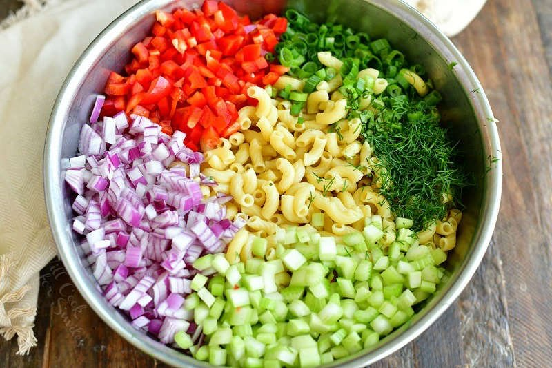 ingredients in a metal mixing bowl laid in side by side: macaroni, chopped pepper, chopped onions, chopped celery, green onions and herbs