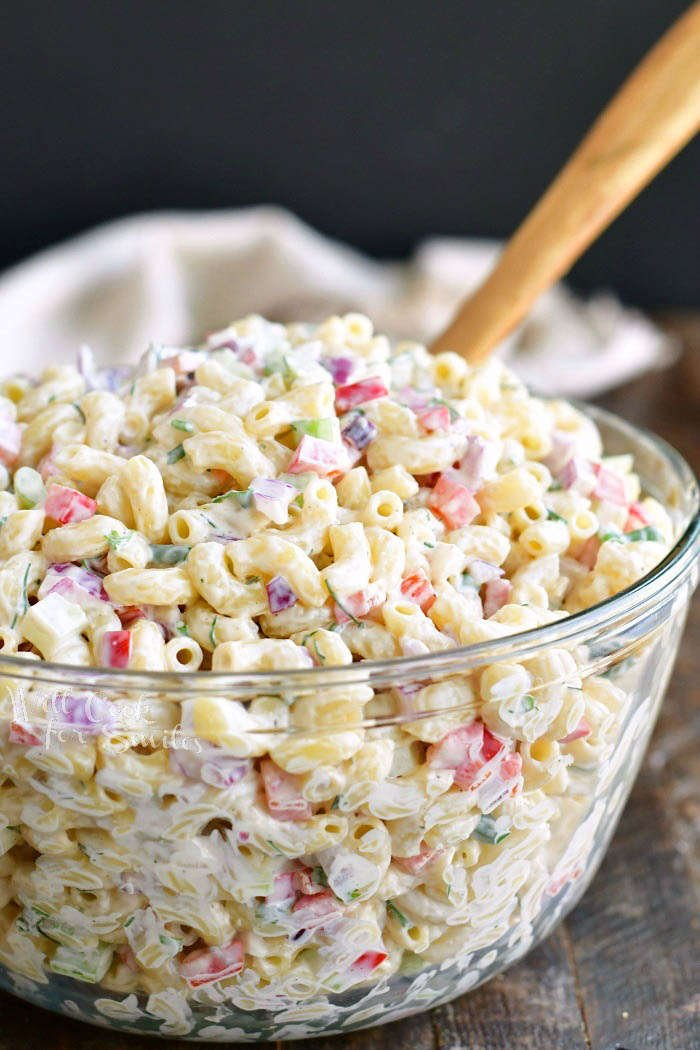 side view of prepared macaroni salad in a glass bowl with a wooden spoon