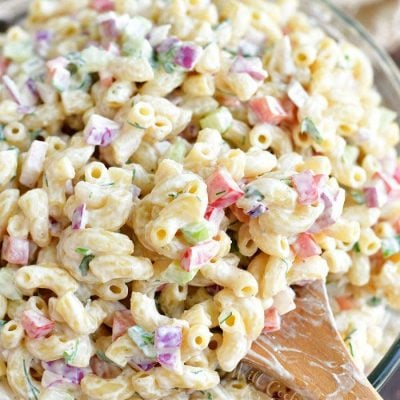 scooping prepared macaroni salad with a wooden spoon