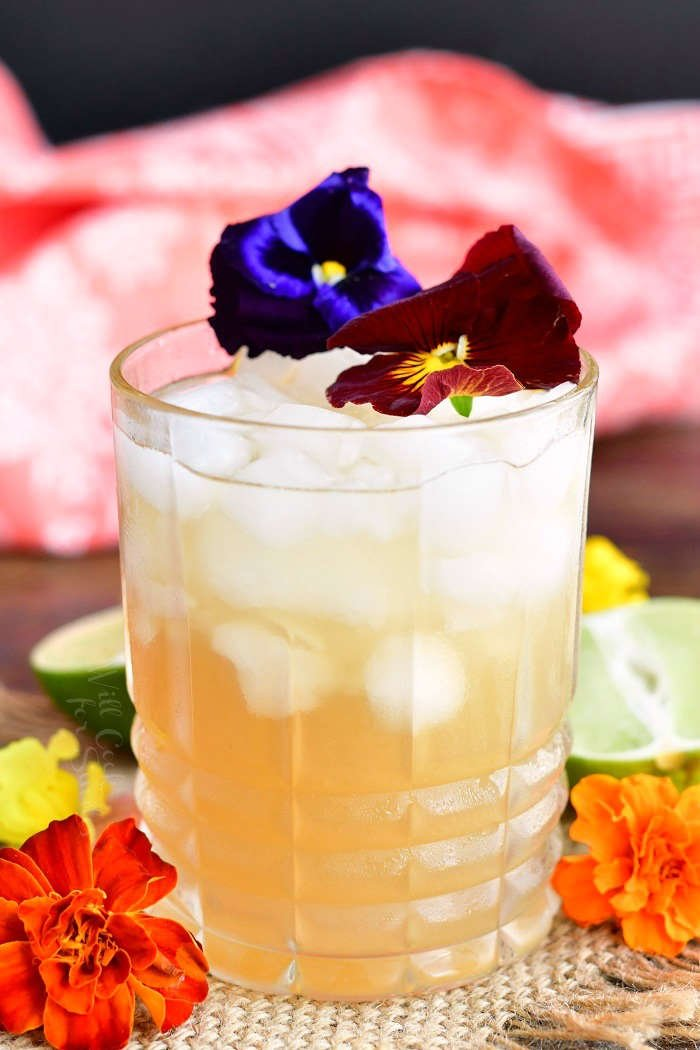closeup of glass filled with crushed ice and light yellow cocktail decorated with purple and burgundy flowers