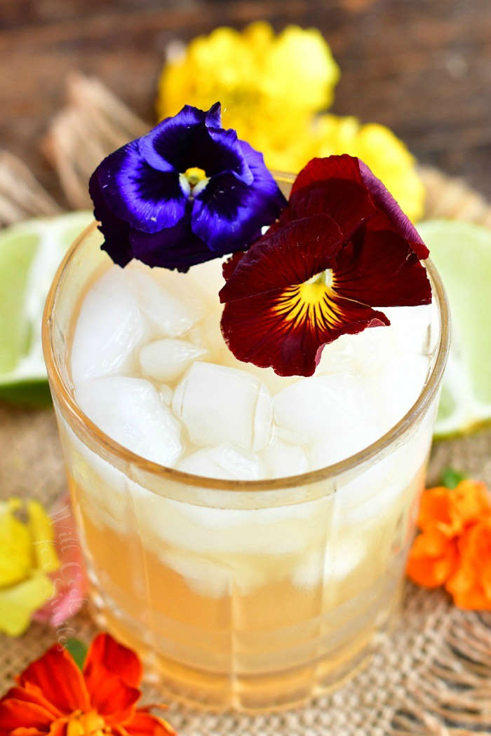 top view of cocktail in the glass with crushed ice and two flowers on top