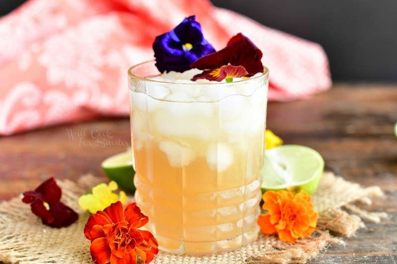 horizontal side view of the yellowish cocktail in a glass topped with two flowers and more orange flowers around the glass