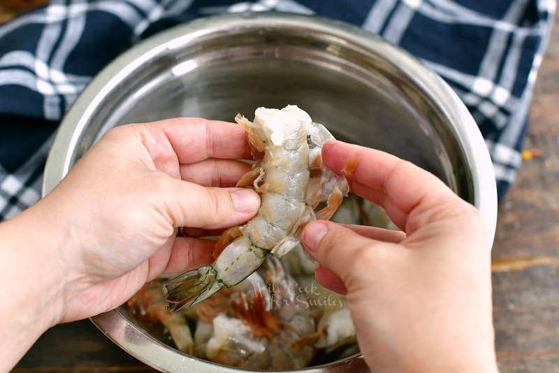 holding a shrimp and peeling off the shell