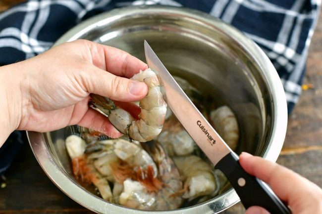 holding the shrimp and cutting through the top with a small knife