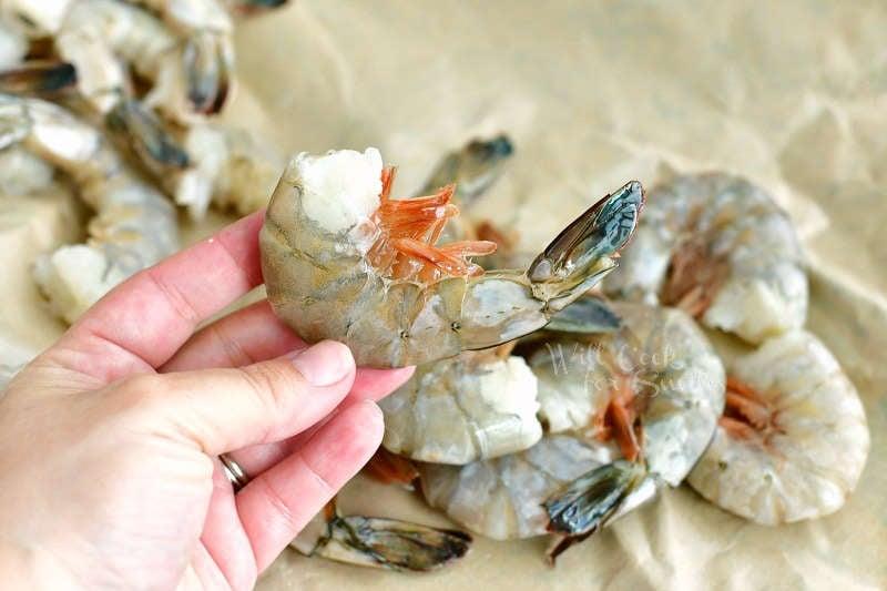 holding a shrimp still in a shell