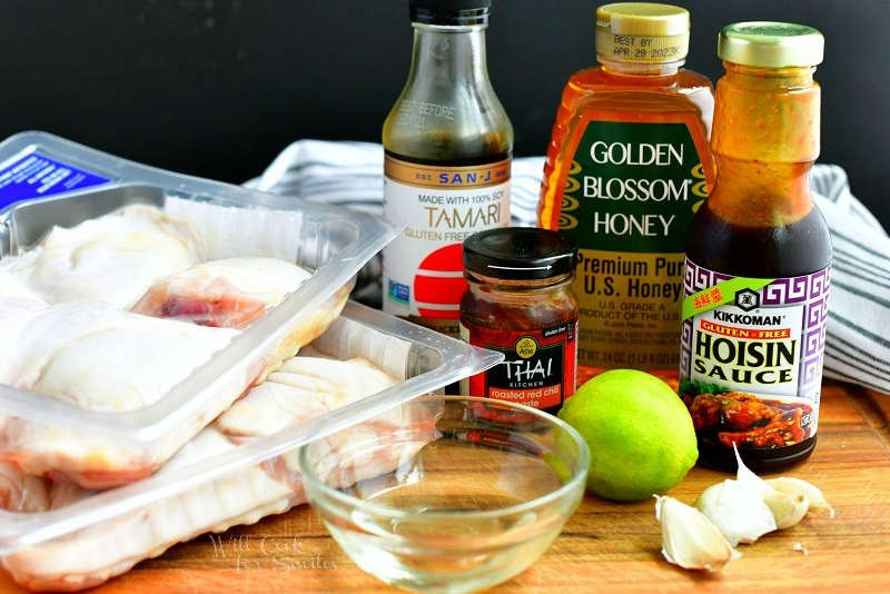 ingredients for baked chicken thighs on a cutting board including 2 packages of chicken thighs, soy sauce, honey, hoisin sauce, chili paste, lime, garlic cloves, and vinegar.