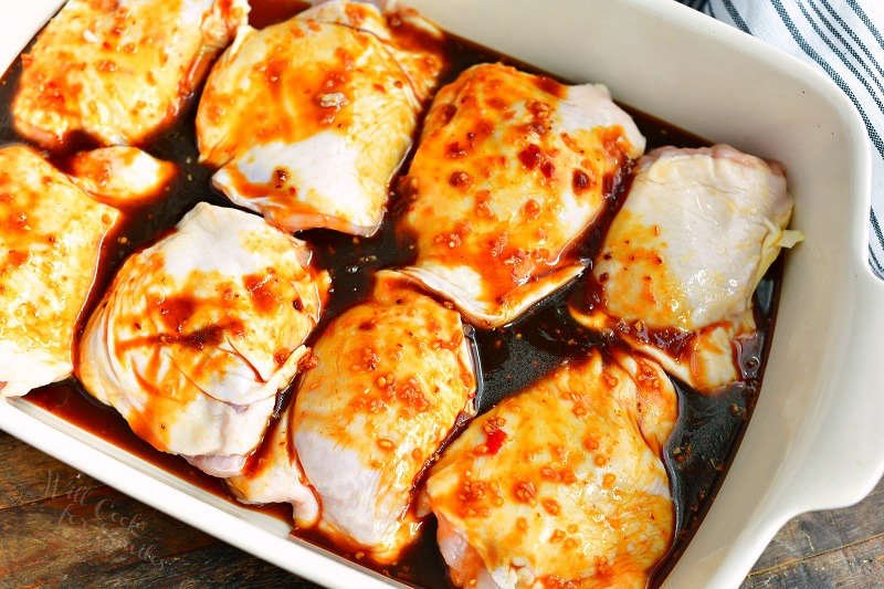 uncooked chicken thighs covered with dark brown sauce in a white baking dish