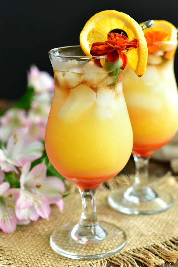 side view of layered cocktail pink on the bottom, orange in the middle, and dark clear on top garnished with a flower and orange slide and cherry