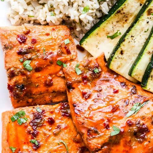 three pieces of salmon on a plate with rice and zucchini slices