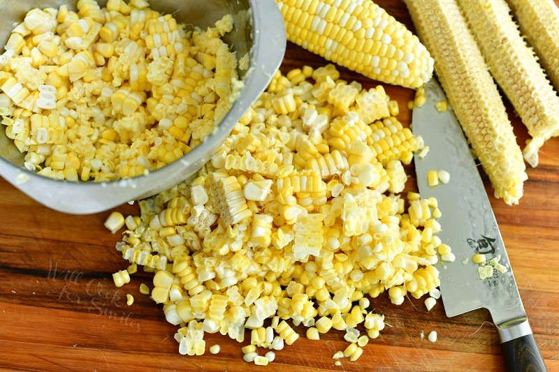 corn on a cob and corn kernels cut off the cob on the cutting board with a knife and a bowl of some corn kernels in it