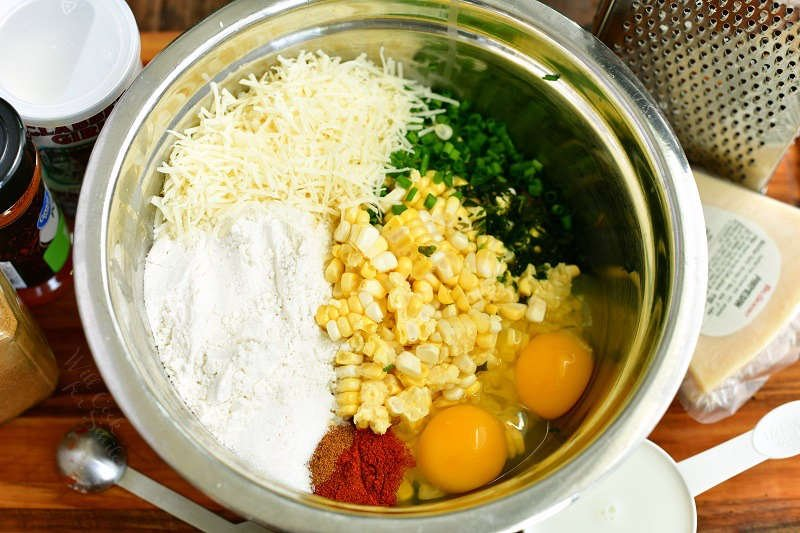 ingredients for the corn mixture side by side inside a mixing bowl and surrounding the bowl on the cutting board