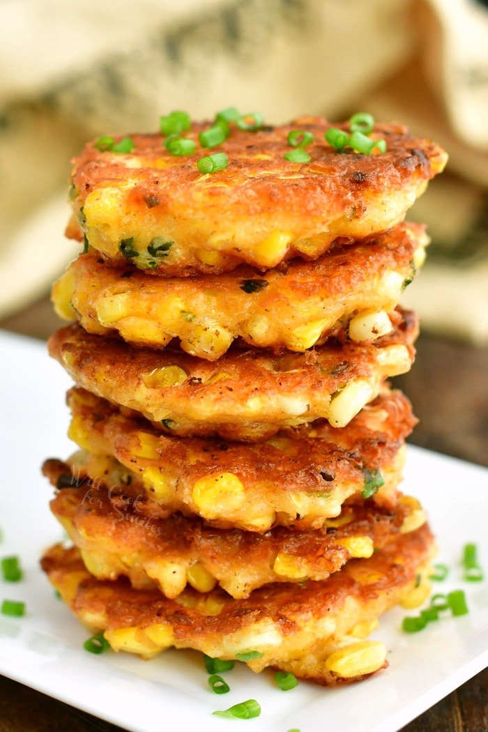 stacked corn fritters on a white plate with chives sprinkled on top