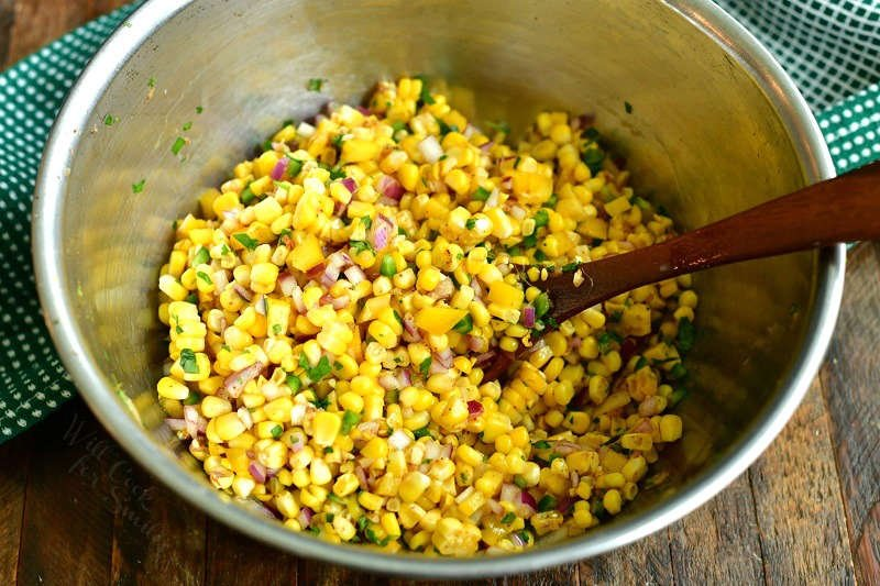 ingredients for corn salsa mixed together in a metal mixing bowl with a wooden spoon