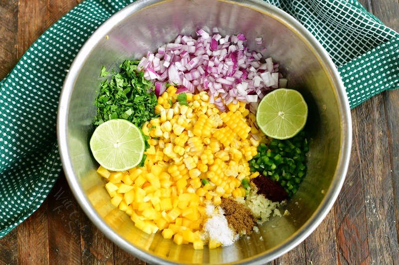 ingredients in a bowl side by side including corn kernels, yellow bell pepper, lime halves, jalapeno, red onion, cilantro, and seasonings