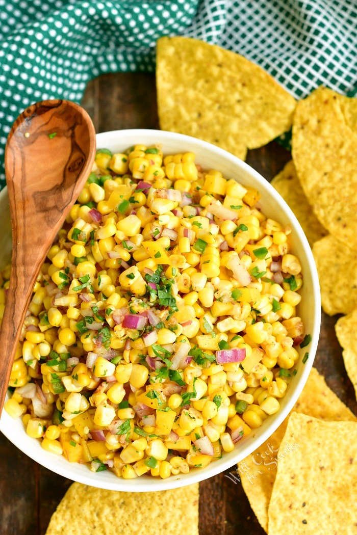 top view of corn salsa in a white bowl with wooden spoon laying on the bowl and chips around it