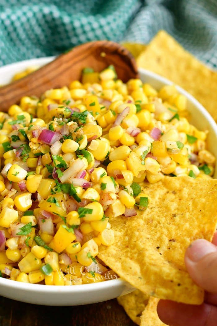 scooping corn salsa with a yellow tortilla chip with green napkin on the background