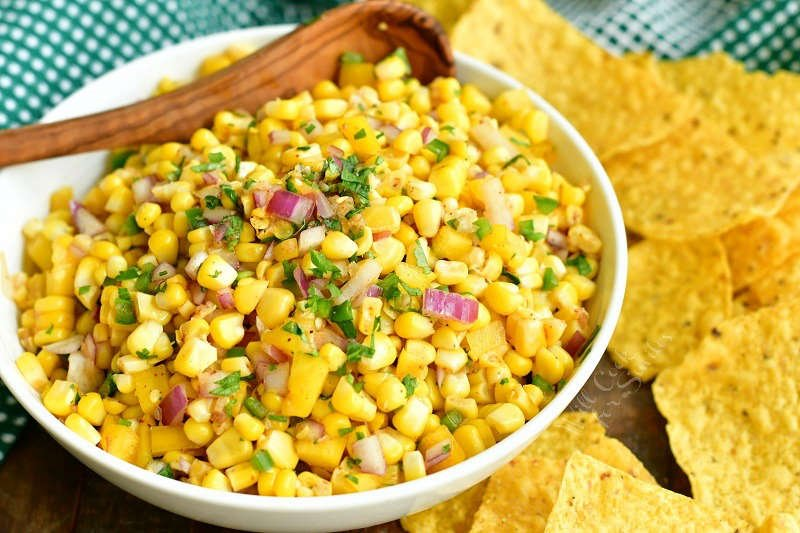 horizontal image of corn salsa in a white bowl with wooden spoon in it and yellow corn tortillas around