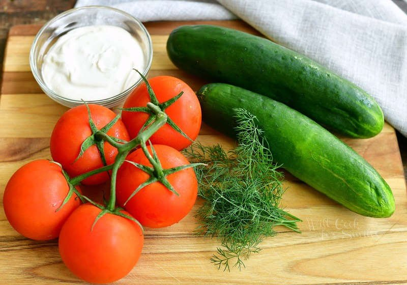 ingredients on the cutting board including two cucumbers, tomatoes on a vine, bunches of dill weed, and a small bowl of sour cream