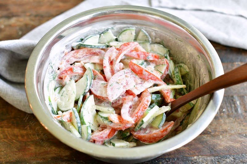 tomatoes and cucumbers with sour cream and dill week mixed together in a metal mixing bowl