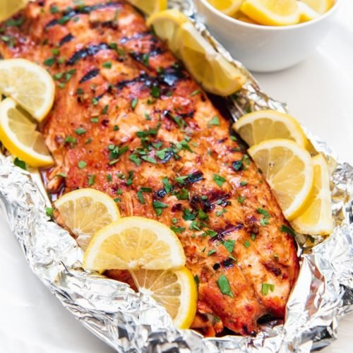 large piece of salmon in foil with lemon slices around it and a small bowl of lemons