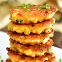 closer view of fried corn fritters stacked on top of each other and some chives on top