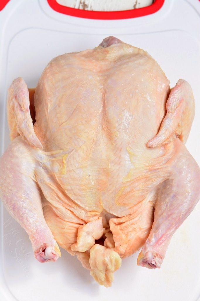 whole raw chicken on a white plastic cutting board
