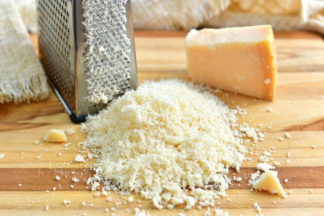 finely grated hard cheese in a mount in the cutting board with box grater and a block of cheese next to it