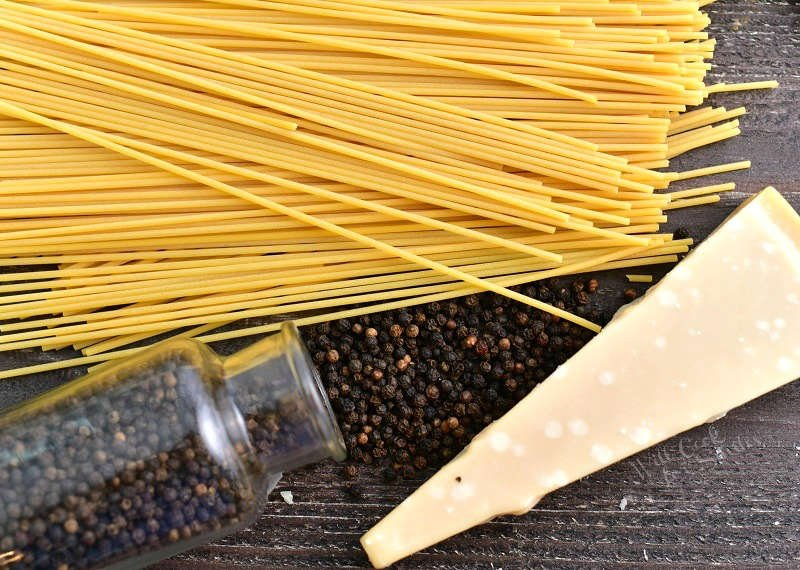 dried thin long pasta, whole peppercorns spilling out of a clear glass jar, and a block of hard cheese on a wooden board
