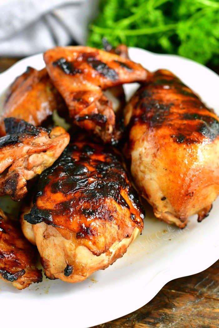 grilled marinated chicken breast wings and legs on a white plate