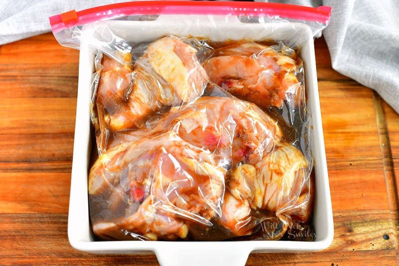 chicken pieces with marinade inside a plastic zip top bag laying inside a white baking dish