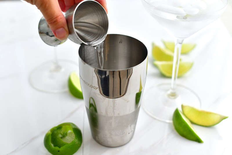 pouring clear vodka into the cocktail shaker out of a silver jigger and martini glass with ice water next to it