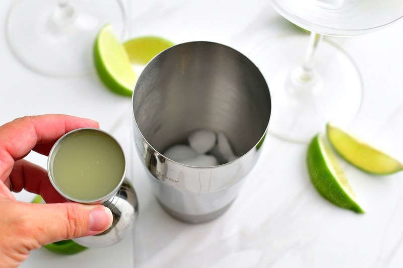 holding fresh lime juice in a metal jigger next to a cocktail shaker with ice and parts of two martini glasses visible