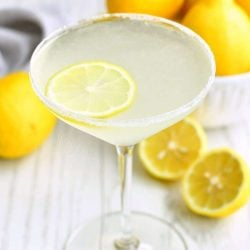martini glass filled with light yellow cocktail with lemon slice floating in it and sugar on the rim. bowl of lemons next to the glass and some lemon on the table