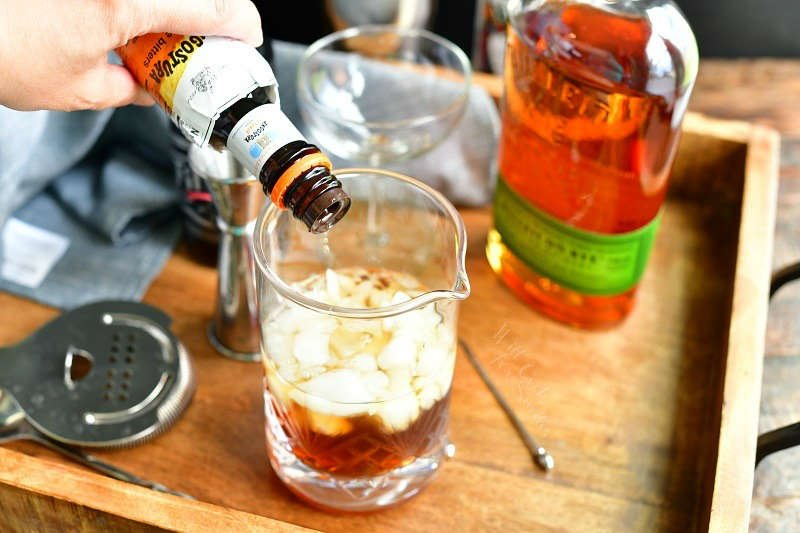 adding dash of bitters into the mixing glass with ice and brown liquors our of a dark brown bottle with bottle of whiskey, glass, jigger, and strainer on the background