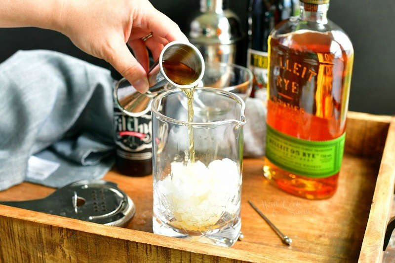 pouring whiskey out of a silver jigger into mixing glass filled with crushed ice. bottle of whiskey on the background with a jar of cherries and sweet vermough