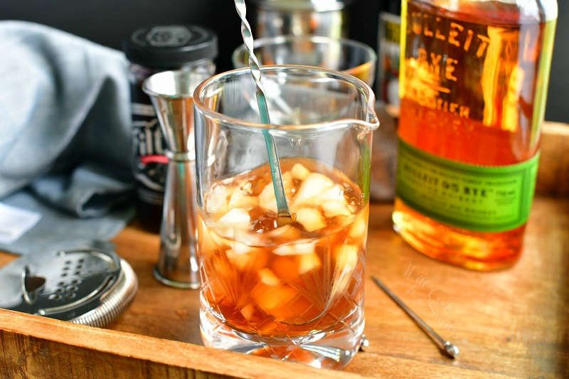 stirring the brown cocktail with ice in a mixing glass using a cocktail long spoon with bottles in the background, strainer and jigger