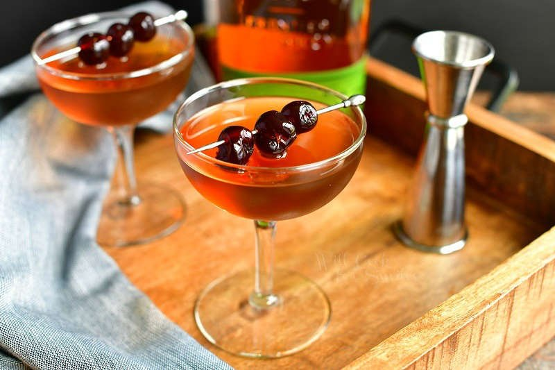 Manhattan cocktail in a glass in the center of the image topped with dark cherries on a silver pock with another glass to the left, a bottle of whiskey on the background and a silver jigger to the right