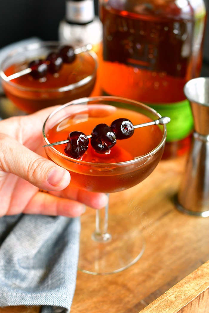 holding a Manhattan cocktail topped with three cherries on a silver pick with another glass on the background and a bottle of whiskey