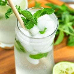 top view of mojito cocktail in a curvy glass with a paper straw and mint sprig